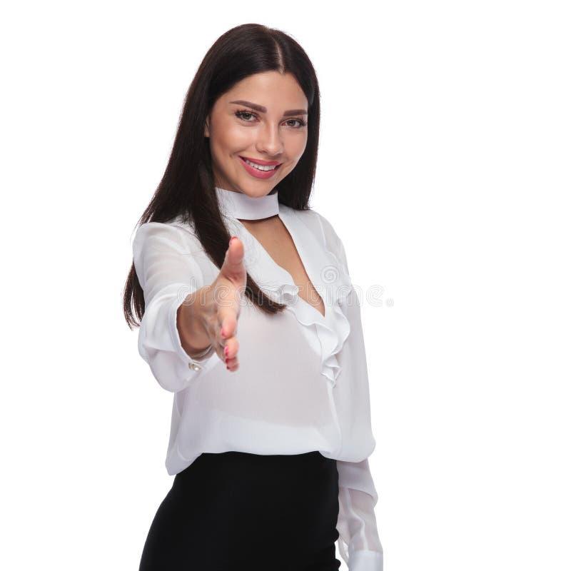 Den härliga brunettaffärskvinnan önskar att skaka din hand royaltyfri foto