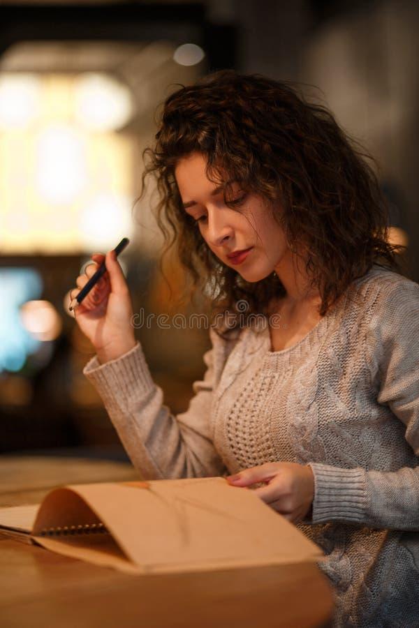Den härliga brunettaffärskvinnan gör anmärkningar i hennes notepad i hemtrevlig restaurang iklädda grå färger stucken sweather royaltyfri bild
