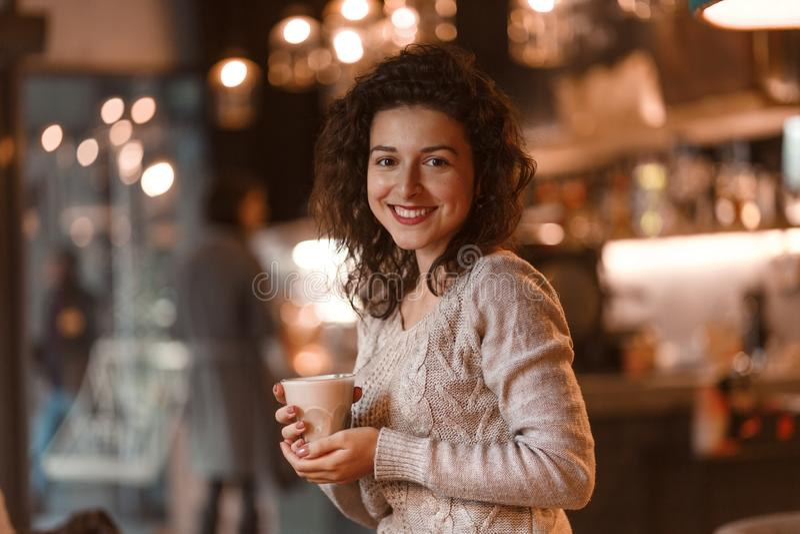 Den härliga brunettaffärskvinnan gör anmärkningar i hennes notepad i hemtrevlig restaurang iklädda grå färger stucken sweather arkivfoto