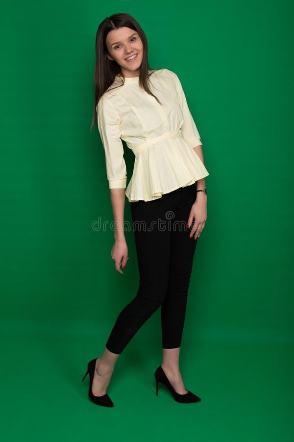 Den härliga brunetten i en gul blus och svart flåsar på en gräsplan royaltyfri fotografi