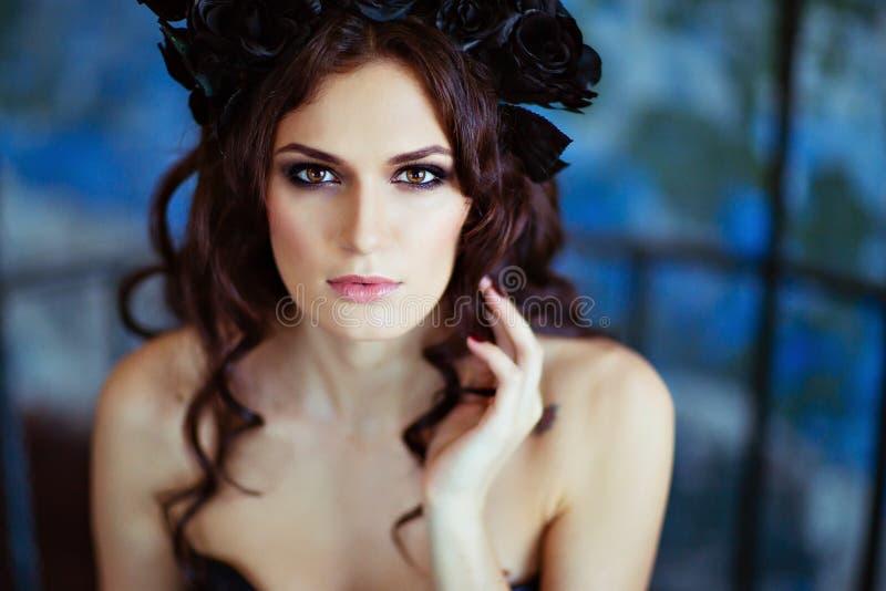 Den härliga brunetten med en krans av svart blommar sammanträde på ett b royaltyfri foto