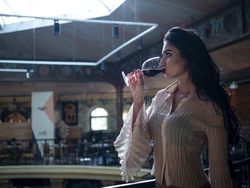 Den härliga brunetten med långt hår dricker anseende från ett exponeringsglas av rött vin inomhus arkivfoto