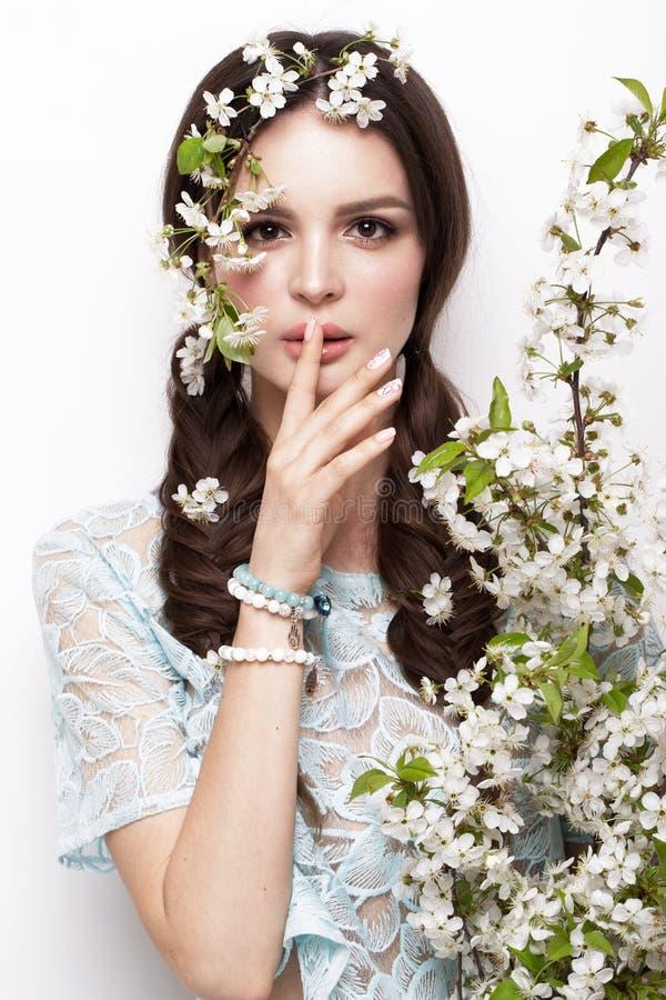 Den härliga brunettflickan i blått klär med ett försiktigt romantiskt smink, rosa kanter och blommor Skönheten av framsidan royaltyfria foton