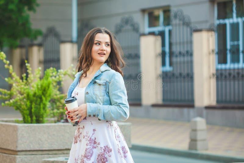 Den härliga brunettflickan i ett jeansomslag går runt om staden med kaffe i händer arkivfoton