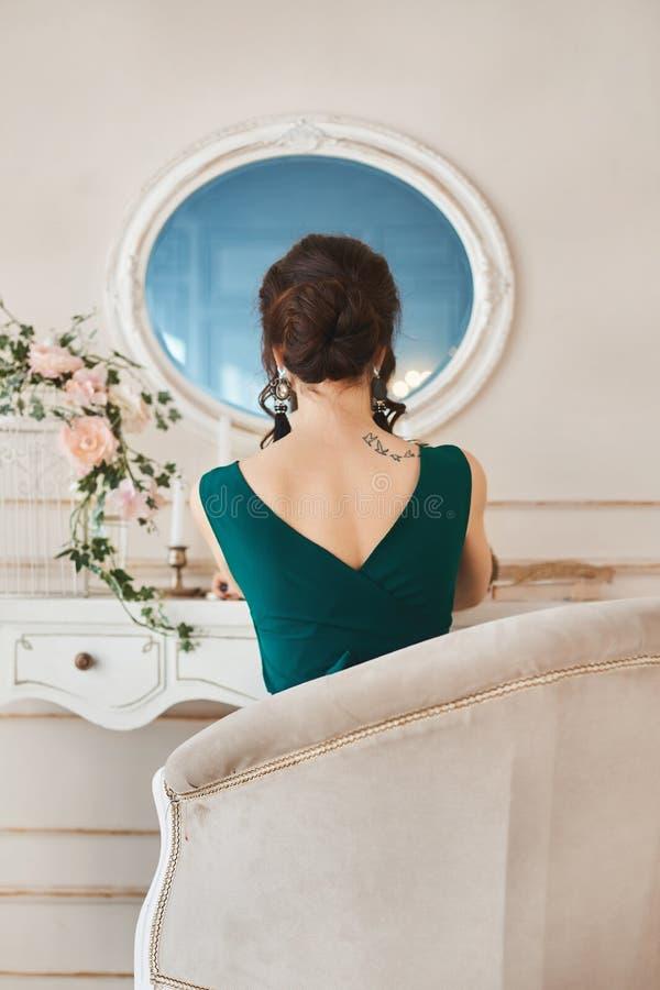 Den härliga brunettflickan i klänning sitter tillbaka till kameran och ser i spegel arkivbilder