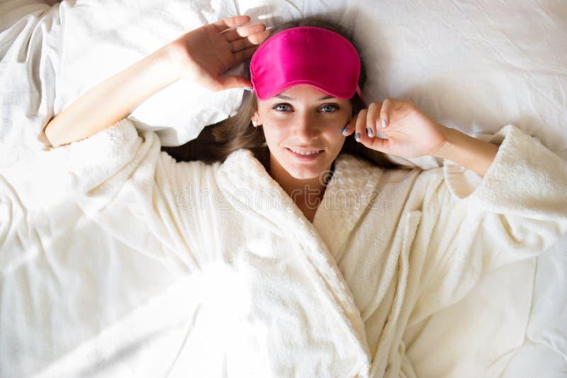 Den härliga brunettflickan ligger i säng i en maskering för sömn bara upp vaknade royaltyfria bilder