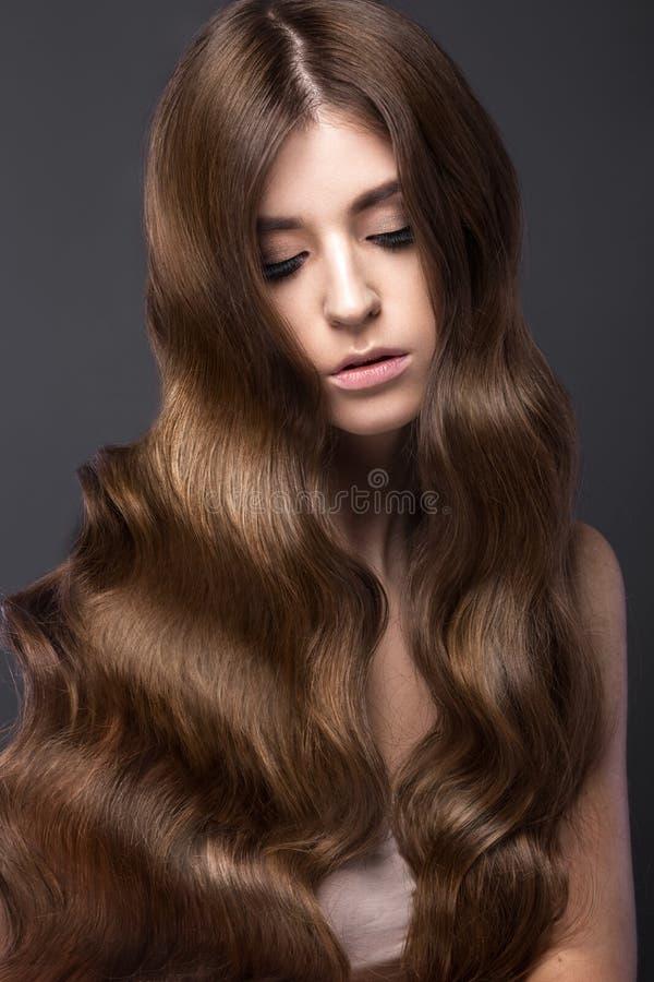 Den härliga brunettflickan med krullar perfekt hår- och klassikersmink Härlig le flicka arkivfoton