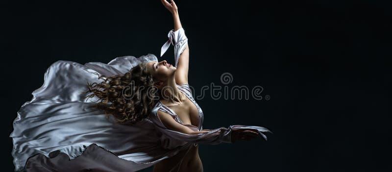 Den härliga brunettflickan med lockigt hår i mörkret och ljus i sexigt silversatängflyg klär enormt poserar i dans royaltyfria foton