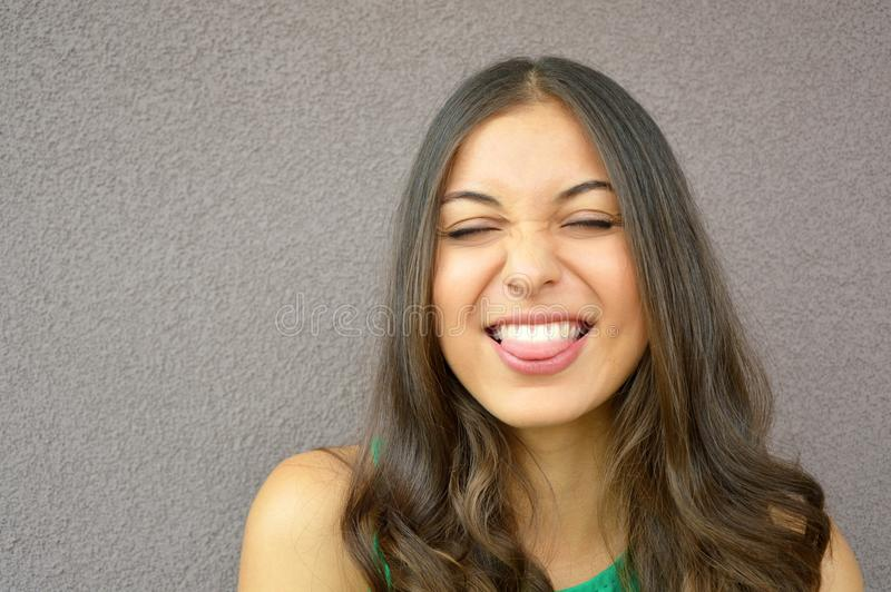 Den härliga brunettflickan stänger henne ögon- och showtungan på isolatcopyspaceviolet royaltyfri fotografi