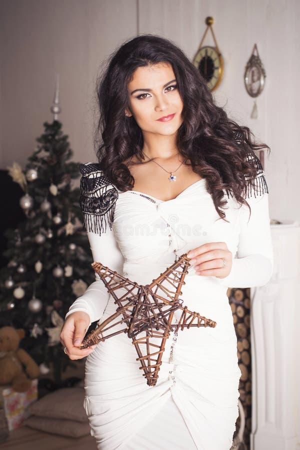 Den härliga brunettkvinnan i den vita klänningen i nytt år dekorerade in arkivfoto