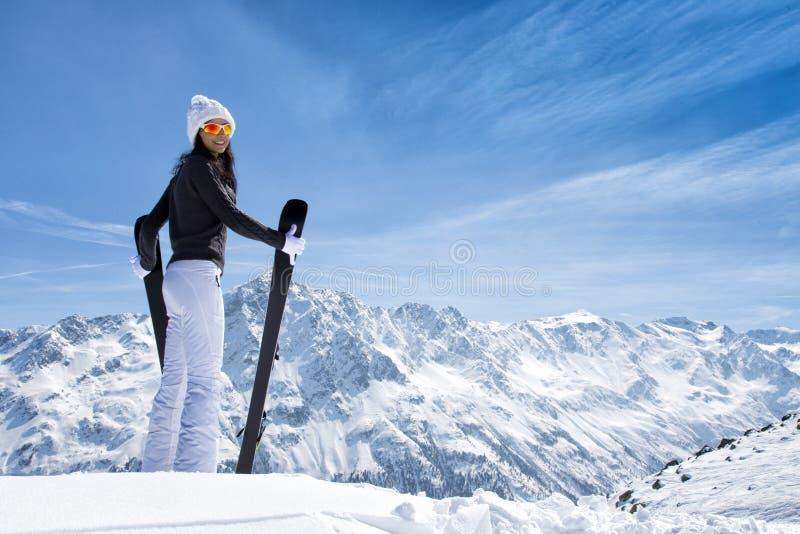 Den härliga brunettkvinnan med skidar royaltyfri bild