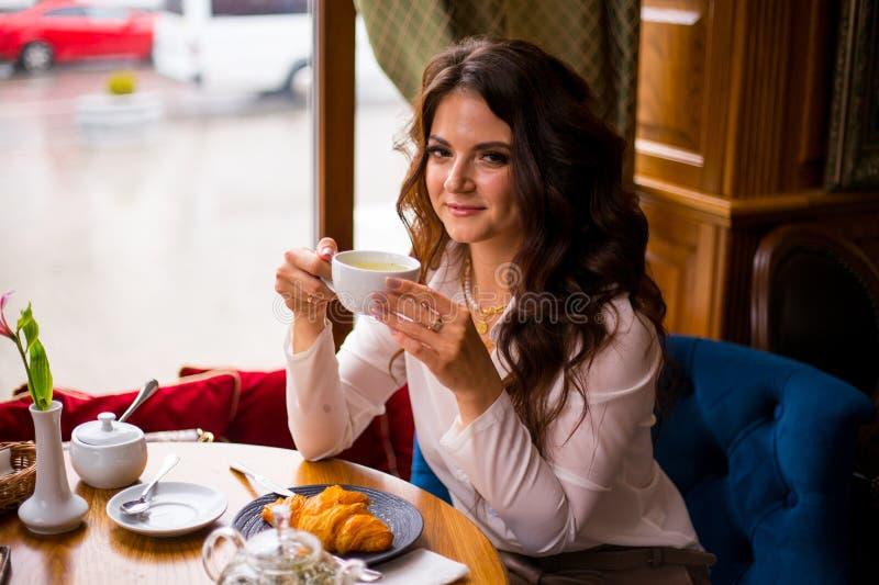 Den härliga brunettkvinnan som dricker te i stadskafé och, äter franska giffel för frukost royaltyfri foto