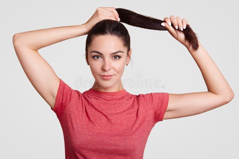 Den härliga brunettkvinnlign trycker på ponnysvansen, har sund hud, iklädd tillfällig t-skjorta, har smink, vilar hemma, visar he arkivbild