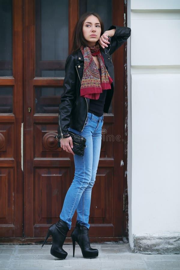 Den härliga brunhåriga kvinnan med en halsduk på höga häl arkivfoto
