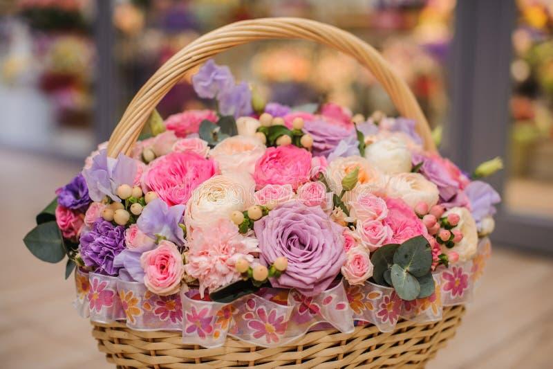 Den härliga buketten av rosa färger, lilor blommar i korg arkivbilder