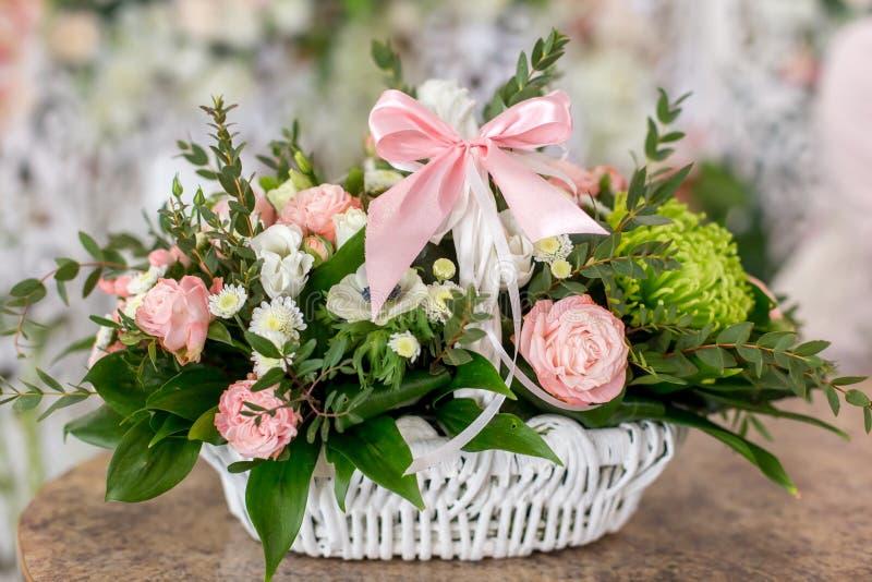 Den härliga buketten av rosor i den vita korgen är på en tabell i blommaboutique arkivfoton