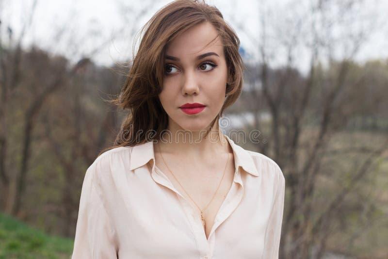 Den härliga caucasian flickan med röda kanter, lockigt hår i stilfull beige blus ser hänsynsfullt åt sidan Enkelt tr?d i dimma royaltyfri bild