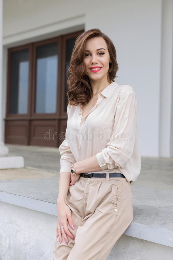Den härliga caucasian flickan med röda kanter och lyckligt leende i stilfull beige blus ser in camera och att posera utomhus arkivfoto