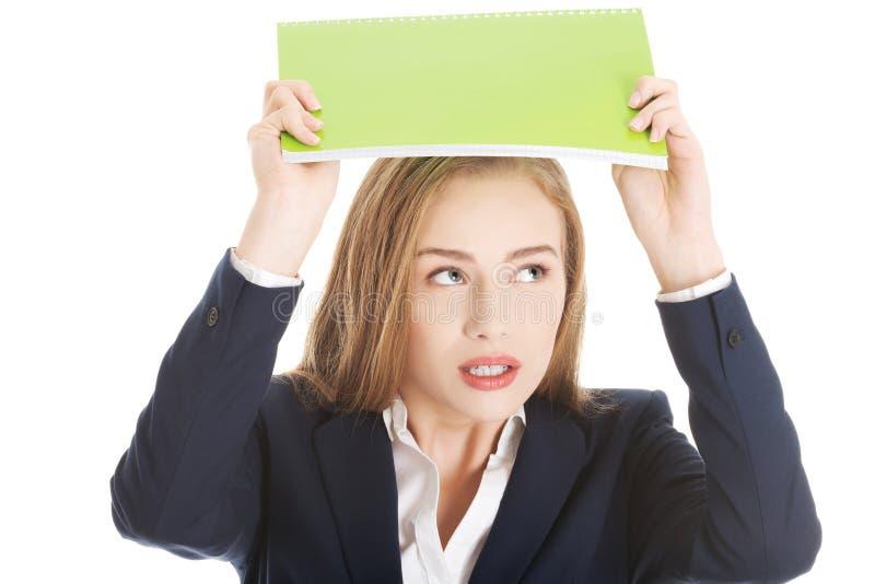 Den härliga caucasian kvinnan är den hållande anteckningsboken över hennes huvud som är pro- royaltyfria foton