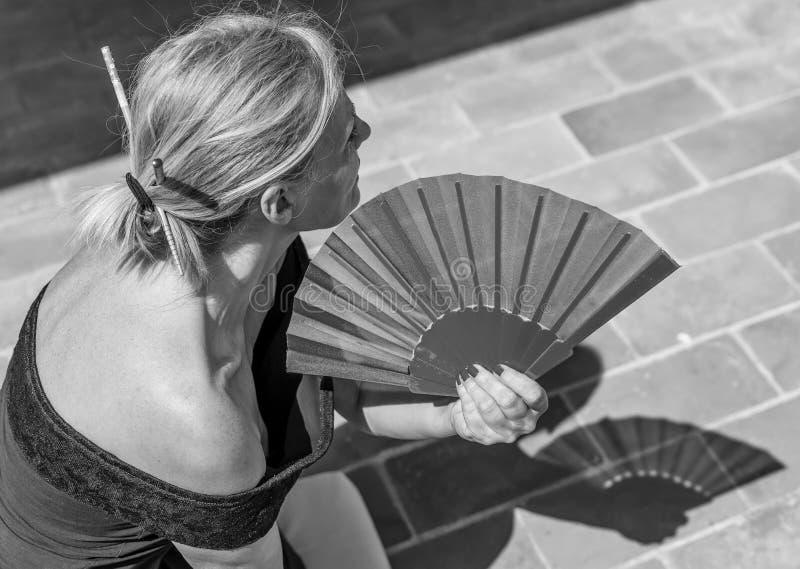 Den härliga caucasian kvinnan använder en handfan för att kyla av på en varm sommardag arkivbild