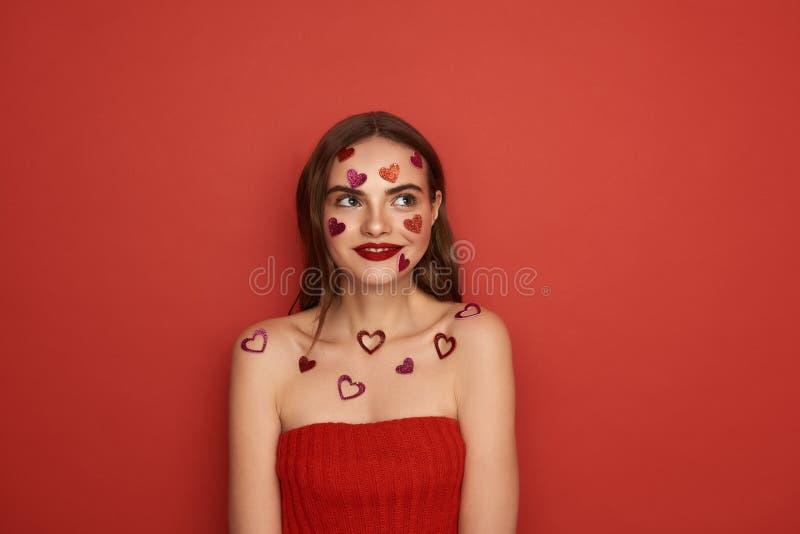 Den h?rliga Caucasian kvinnan dekoreras med r?da hj?rta-formade klisterm?rkear p? f?rgbakgrund arkivfoto