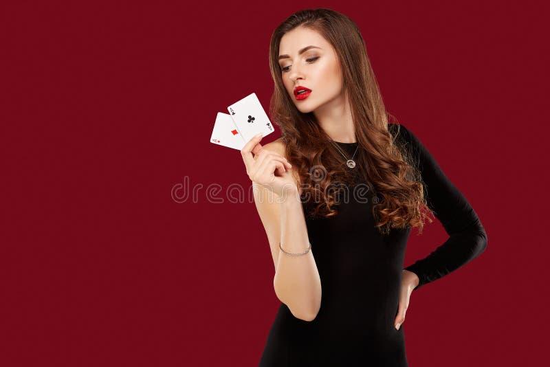 Den härliga caucasian kvinnan i svart klänning med poker cards dobbleri i kasino fotografering för bildbyråer
