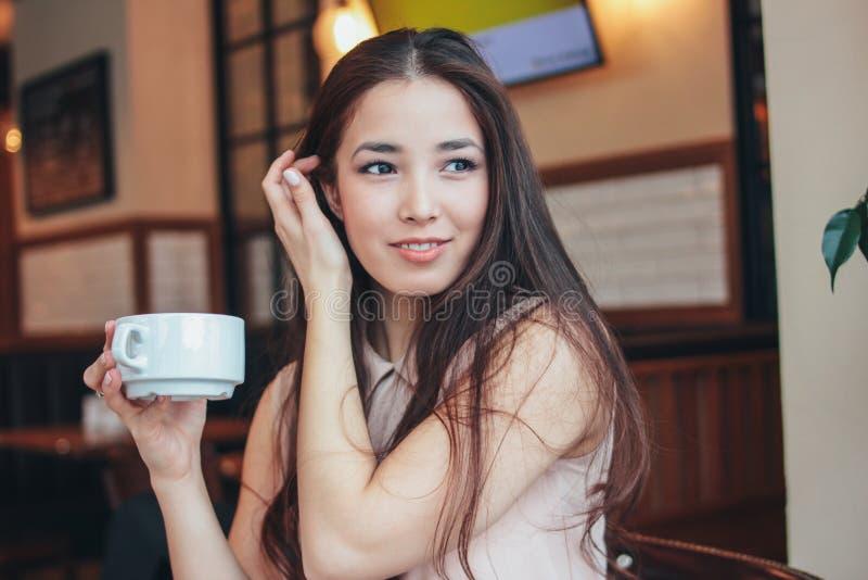 Den härliga charmiga romantiska brunetten som ler den asiatiska flickan, har frukosten med kaffe på kafét arkivbild