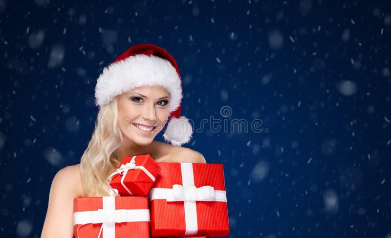Den härliga damen i jullock rymmer en uppsättning av gåvor royaltyfri bild