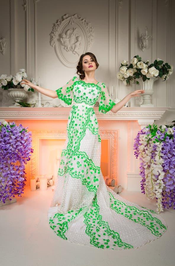 Den härliga damen klädde den lyxiga klänningen med ett drevanseende i den eleganta vita inre som dekorerades av naturliga blommor arkivbild