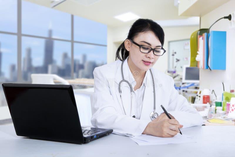 Den härliga doktorn skriver receptet på kliniken arkivbilder