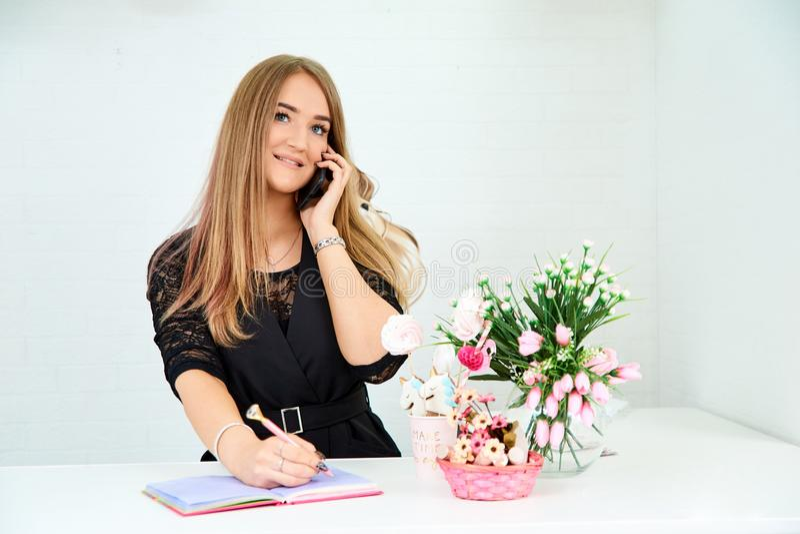den härliga europeiska flickan tar en appell på telefonen och skriver i en anteckningsbok på en vit bakgrund Närliggande är blomm royaltyfria bilder