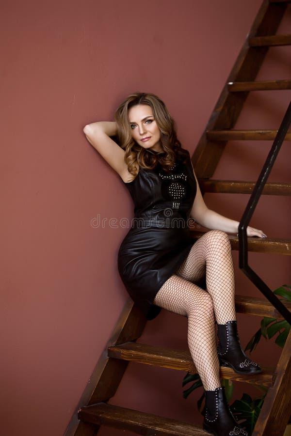 Den härliga europeiska medelåldersa kvinnan i svart klänning sitter på trappan, nätt caucasian kvinna med mörkt krabbt royaltyfri foto