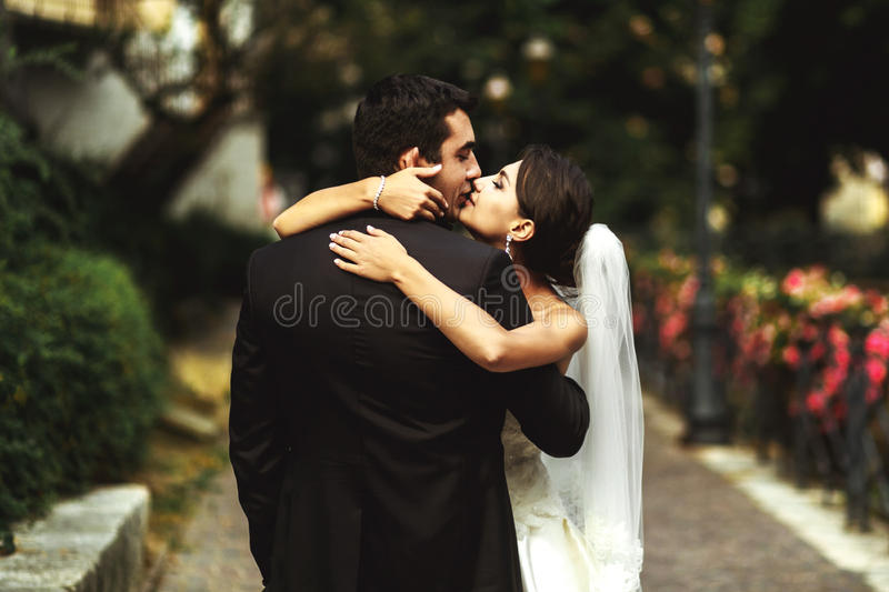 Den härliga exotiska brunettbruden som kramar den stiliga brudgummen parkerar in, n royaltyfri bild