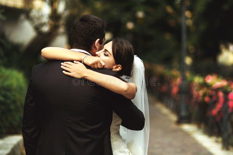 Den härliga exotiska brunettbruden som kramar den stiliga brudgummen parkerar in, n fotografering för bildbyråer