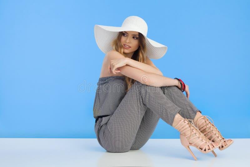 Den härliga för den In Jumpsuit And för modemodellen hatten vita solen är sitta och se bort över skuldra fotografering för bildbyråer