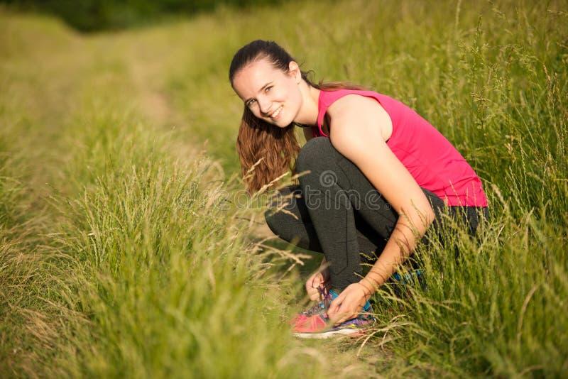 Den härliga för löparebandet för den unga kvinnan skon snör åt för körd genomkörare arkivfoto