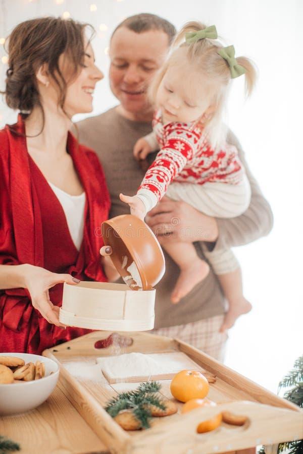 Den härliga familjen med behandla som ett barn flickan som förbereder degen för pajen arkivbild