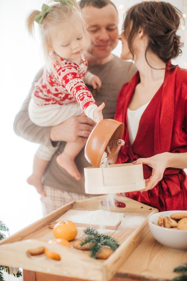 Den härliga familjen med behandla som ett barn flickan som förbereder degen för pajen royaltyfri foto