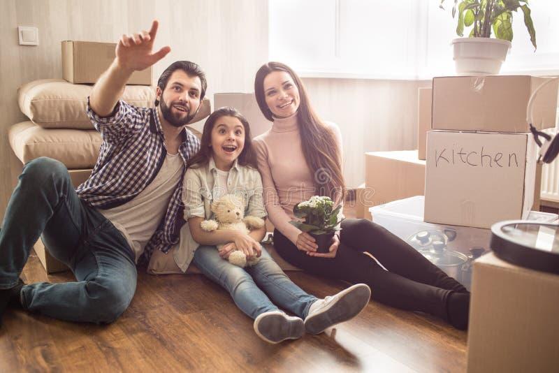 Den härliga familjen sitter tillsammans på golvet och ser rak framåt man som pekar upp barn Hans flickablickar royaltyfria foton