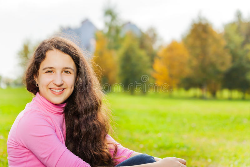 Den härliga flickanärbildsikten sitter på grönt gräs fotografering för bildbyråer