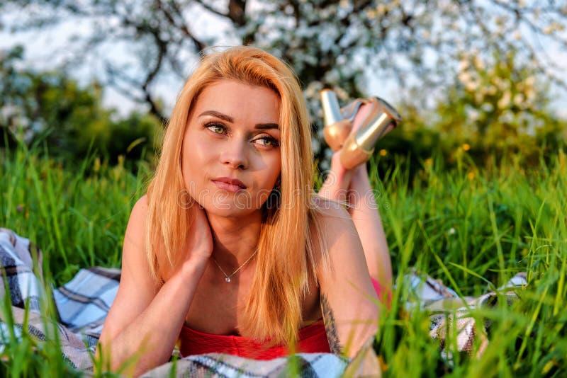 Den härliga flickan är på det gröna gräset royaltyfria bilder