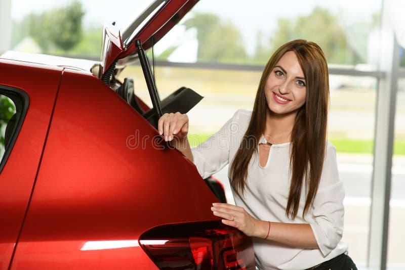 Den härliga flickan armbågar hennes händer på den nya bilen fotografering för bildbyråer
