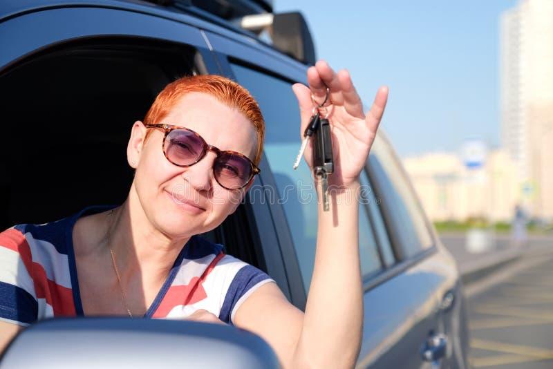 Den härliga flickan blev den lyckliga ägaren av den nya bilen Hålltangenter i hans händer som ler till att skela från solen royaltyfri foto