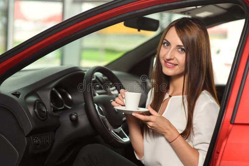 Den härliga flickan dricker kaffe i den nya bilen royaltyfri foto