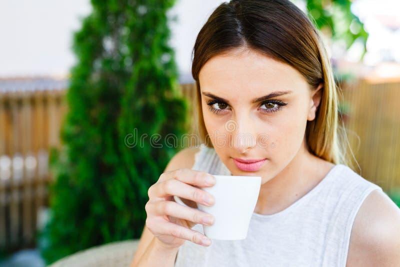 Den härliga flickan dricker kaffe, medan sitta på trädgården för kafé` s arkivfoton