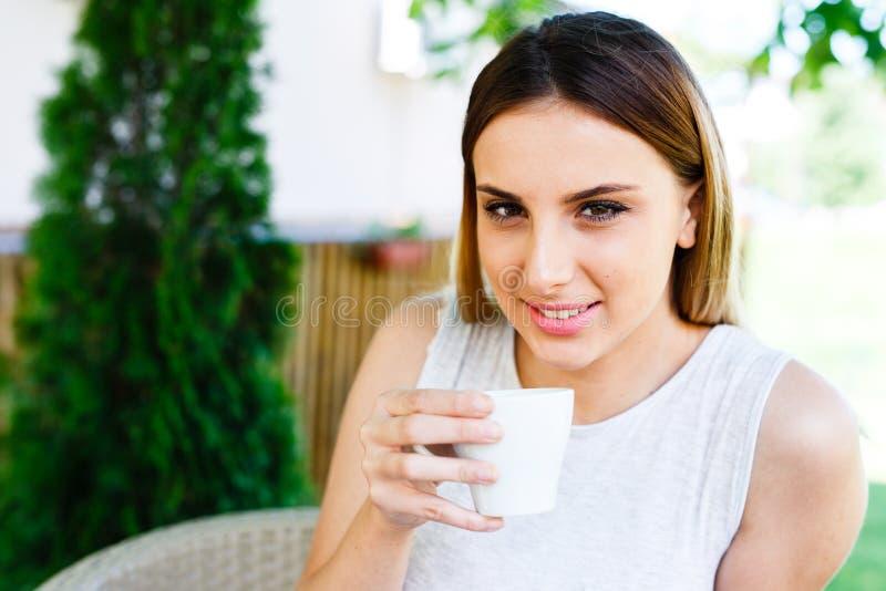 Den härliga flickan dricker kaffe, medan sitta på trädgården för kafé` s arkivfoto