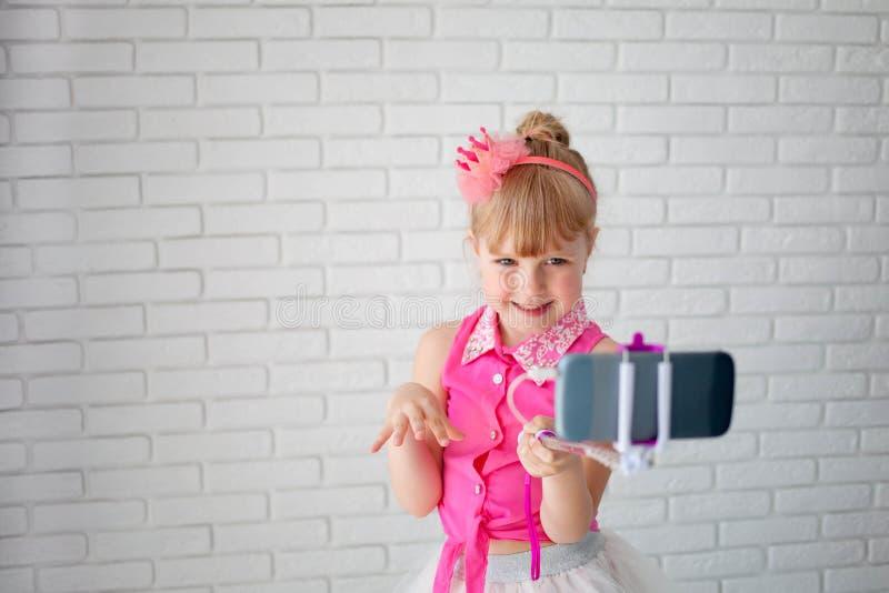 Den härliga flickan en krona tar en selfie på telefonen Barnet skjuter videoen på kanalen, den unga bloggeren royaltyfri bild