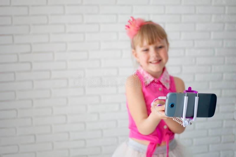 Den härliga flickan en krona tar en selfie på telefonen Barnet skjuter videoen på kanalen, den unga bloggeren arkivfoton