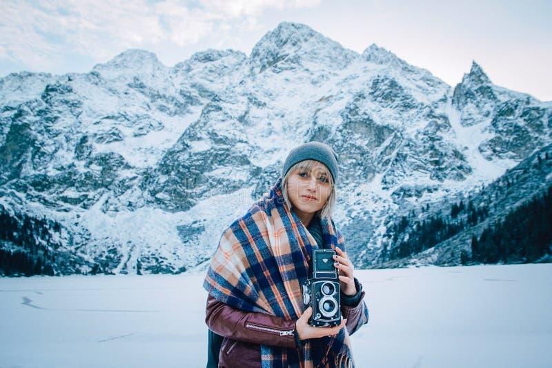 Den härliga flickan gör ett foto på en gammal tappningkamera Äventyra och resa i bergen i vinter arkivbilder