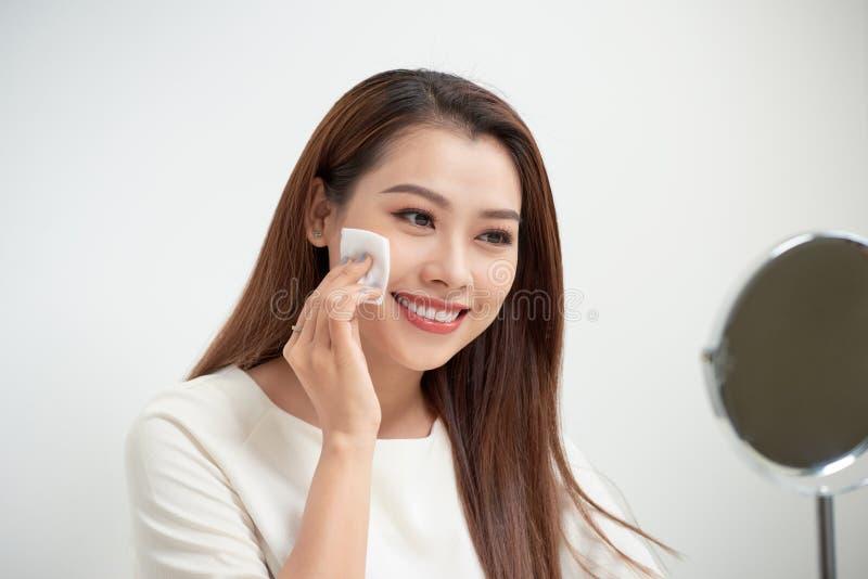 Den härliga flickan gör ren framsidan av makeup med ett bomullsblock royaltyfri fotografi